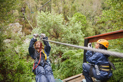Woman zip lining above trees