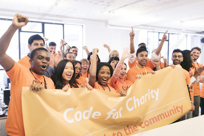 Hackers cheering with banner, coding at hackathon