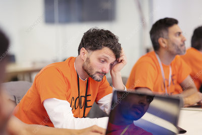 Focused hacker coding for charity at hackathon