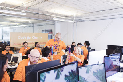 Hackers with lanyards coding at hackathon