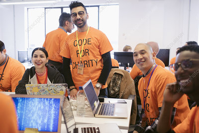 Portrait hackers coding for charity at hackathon