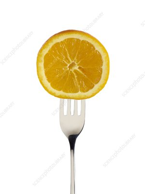 Orange cut in half on a fork