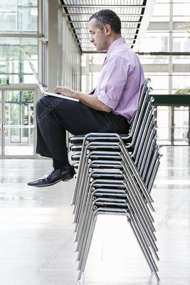 Businessman sitting on top of multiple stacked chairs