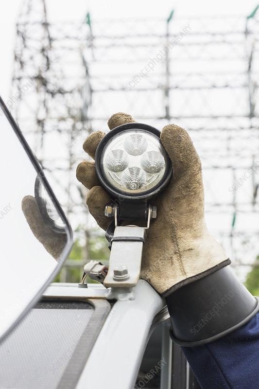 Adjusting work light on vehicle