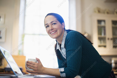 Woman drinking coffee and working at laptop
