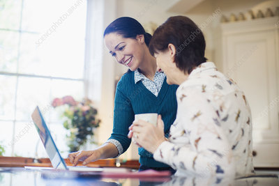 Daughter and senior mother using laptop in kitchen