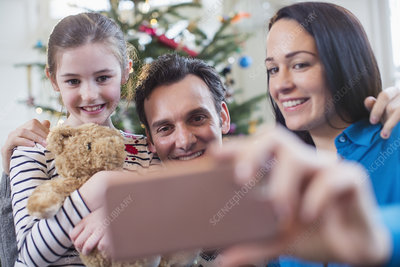 Happy family with smart phone taking selfie