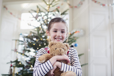 Girl holding teddy bear in front of Christmas tree