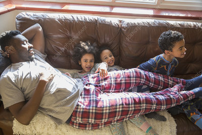 Kids in pyjamas cuddling with father on sofa