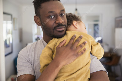 Father holding tired baby son