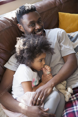 Father cuddling with toddler daughter