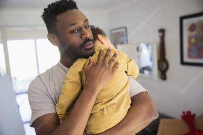 Affectionate father holding tired baby son