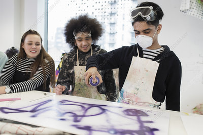 Teenagers spray painting in art class