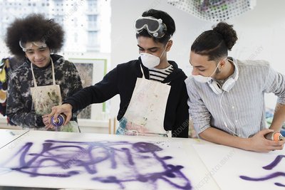 Teenage boys spray painting in art class