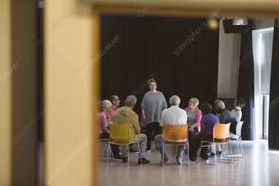 Woman leading seniors in group discussion