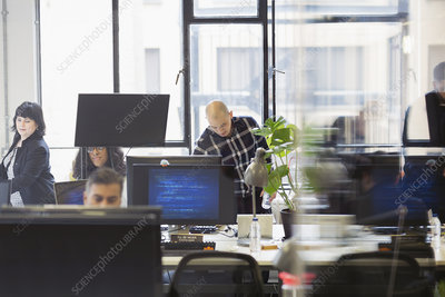Business people working in open plan office