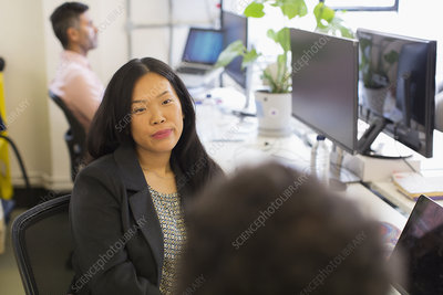 Businesswoman listening to colleague in office