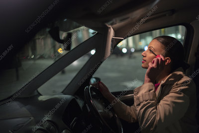 Businesswoman applying mascara in car at night
