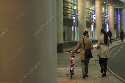 Business people with bicycle walking at night