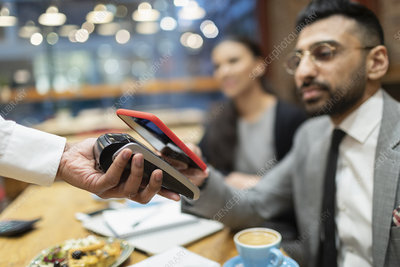 Businessman in cafe paying contactless payment