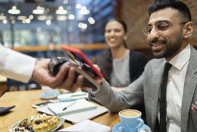 Businessman paying contactless payment in cafe