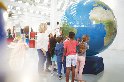 Teacher and students touching large globe
