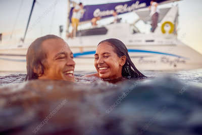 Happy young adult couple swimming in ocean