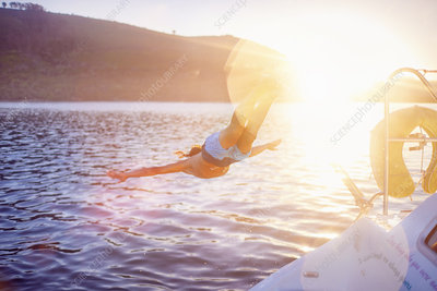 Woman jumping off boat into sunny ocean
