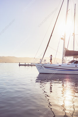 Woman standing on sunny boat in harbour