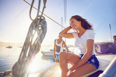 Happy young woman relaxing on sunny boat