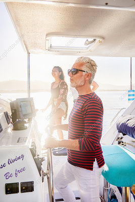 Man at helm on sunny boat