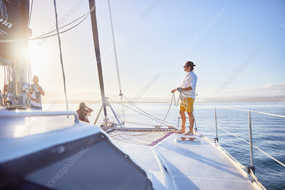 Young man holding rigging rope on sunny catamaran