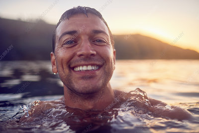 Close up portrait carefree man swimming in ocean