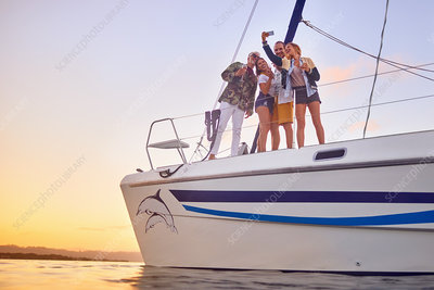 Friends taking selfie on catamaran at sunset