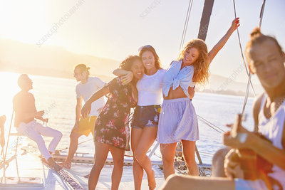 Playful women friends dancing on sunny catamaran