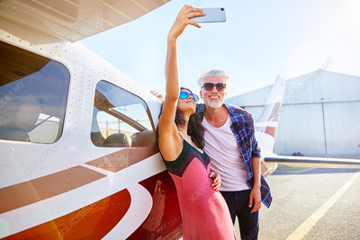Couple taking selfie at small airplane