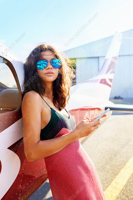 Woman leaning against small airplane