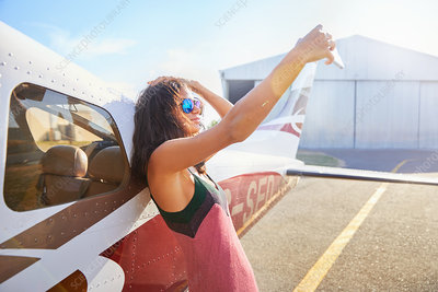 Woman taking selfie with phone at small airplane