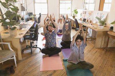 Creative business people practicing yoga in office