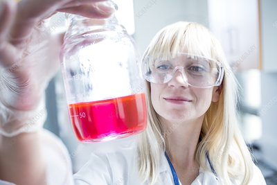 Scientist wearing protective goggles and holding flask