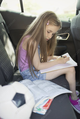 Girl doing homework in back seat of car