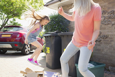 Mother and playful daughter recycling cardboard