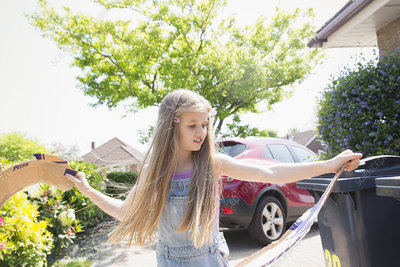 Girl recycling in driveway