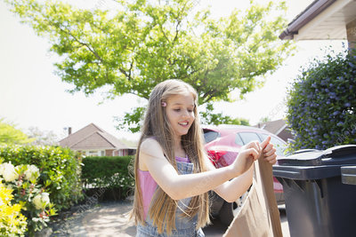 Girl recycling in sunny driveway