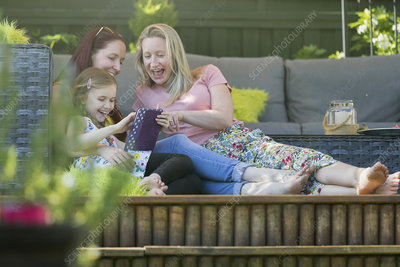 Lesbian couple and daughter using digital tablet