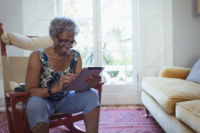 Senior woman using digital tablet in living room