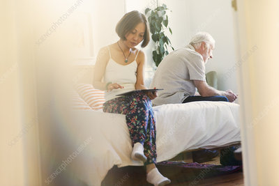 Senior couple using digital tablets in bedroom