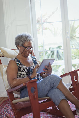 Senior woman using digital tablet in rocking chair