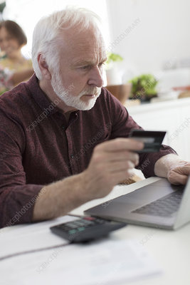 Senior man with credit card at laptop