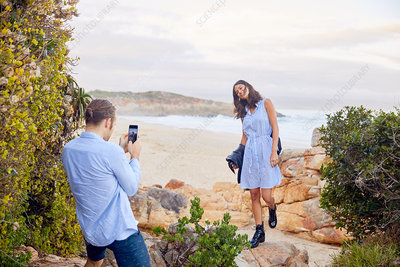 Young man photographing girlfriend